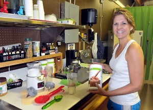 "Tina Wright, Meriden, prepares a smoothie with vitamins, minerals, and protein in the kitchen at ""Healthfully You,"" which she just opened. Photo by Holly Davis"