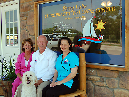 Dr. James Filberth, D.C., with his wife, Janet Sue Filberth, who serves as office manager, and Stacie Madden, massage therapist, with Forrest, the office golden doodle.