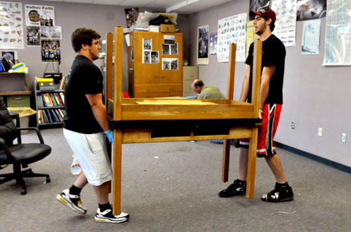 Valley Falls alumni Blake Burns, left, and Jordan Morrow work together to move desks in the high school biology classroom. Workers have been cleaning and renovating rooms all summer.