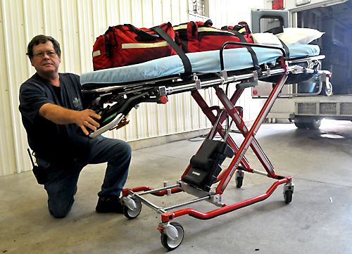 Emergency Medical Director John Gordon demonstrates how to operate a new power cot, one of two acquired by the District 11 EMS unit.