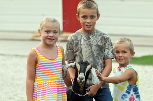 Siblings Sammi, Dallas, and Colby Clark, Valley Falls, smile with their dairy goat, Princess Sophia. Dallas will be showing Miss Sophia at the upcoming 4-H fair.