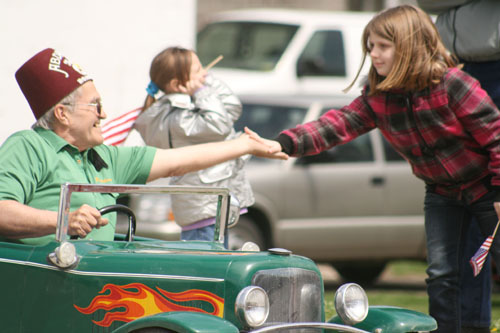 A member of the Abdallah Shriners gets a high five from a young lady watching the Patriots' Day Parade in McLouth. Photos by Dennis Sharkey
