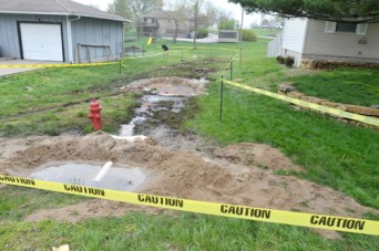 Caution tape defines the areas where diesel fuel overflowed from an underground tank and flowed into a residential neighborhood in McLouth Friday night. Photo by Clarke Davis