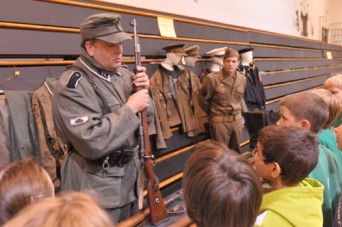 Ed Patterson (top left), Valley Falls, and Dylan Callahan, Emporia, provided a display of World War II uniforms and weapons for students to view during History Day at Valley Falls schools.