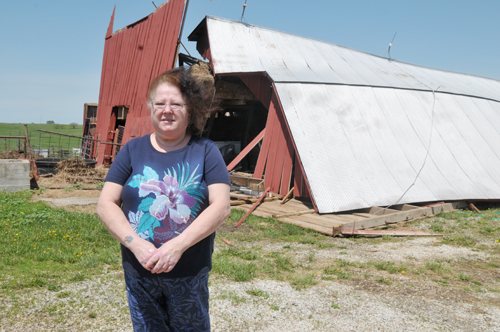 Marsha Funk stands in front of her 100-year-old barn that was standing Sunday morning and later collapsed in the storm. A mare and her colt were in the barn but escaped harm. Photo by Holly Davis