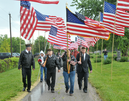 Veterans march through an avenue of wet flags at an Oskaloosa cemetery Monday to pay tribute to the war dead. Photo by Clarke Davis