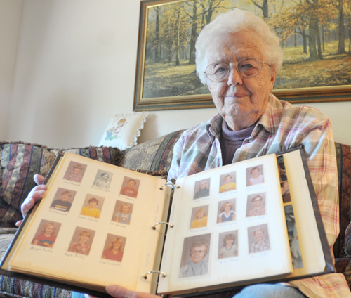 Retired teacher Barbara Tosh holds an album containing the pictures of all of her students. Photo by Holly Davis