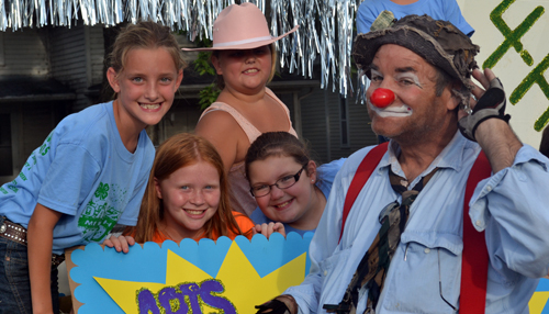 These Valley Victors 4-H'ers ham it up with a clown during the parade. From left are Katelyn Reich, Caitlyn Thomas, Jenna Funk, and RheaAnn Parker, all Valley Falls.