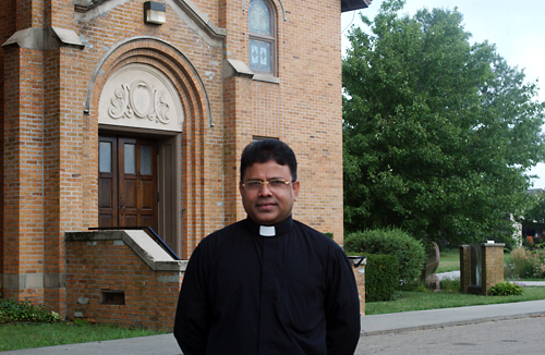 Photo by Jared Speckman New priest Lazar Carasala stands in front of St. Joseph's Church in Nortonville. Carasala is the new priest at St. Joseph's, St. Mary's Immaculate Conception in Valley Falls and Corpus Christi Catholic Church at Mooney Creek.