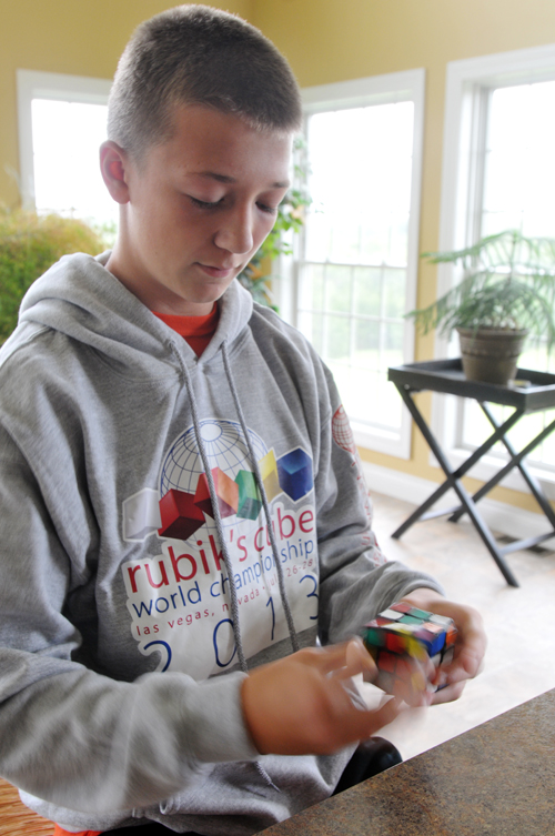 Nathan is pictured solving one of his many Rubik's Cubes. With lots of practice, he doesn't always need to watch what he's doing. At the speed he's going though, it isn't surprising that spring-loaded cubes have popped off during a competition.