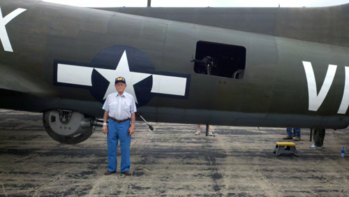 Ted Montgomery poses next to a B-17 bomber that he flew in during World War II.