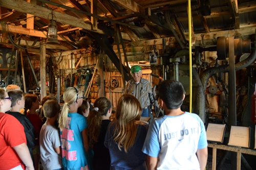 Keith Jackson explains the operation of the blacksmith shop to students on tour at Cottonwood Station Friday. Photos by Clarke Davis