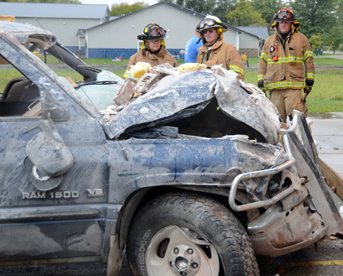 Rock Creek firemen look over the damage to the truck after it was pulled from the clinic.
