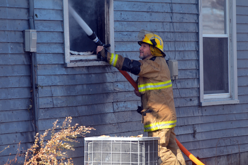 A local firefighter uses water to put out a blaze at a local Winchester house. Photo by Jared Speckman