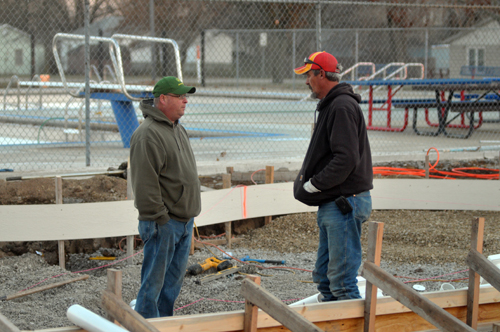 Mayor Eric Hull, left, discusses the ongoing pool project with Monty Hays at the site of the new children's pool Monday evening
