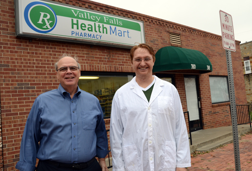 Terry Agler, left, and John Kollhoff were finishing some details on the sale of the Valley Falls Pharmacy Monday. Pharmacists John and Sue Kollhoff bought the business Nov. 5. Photo by Clarke Davis