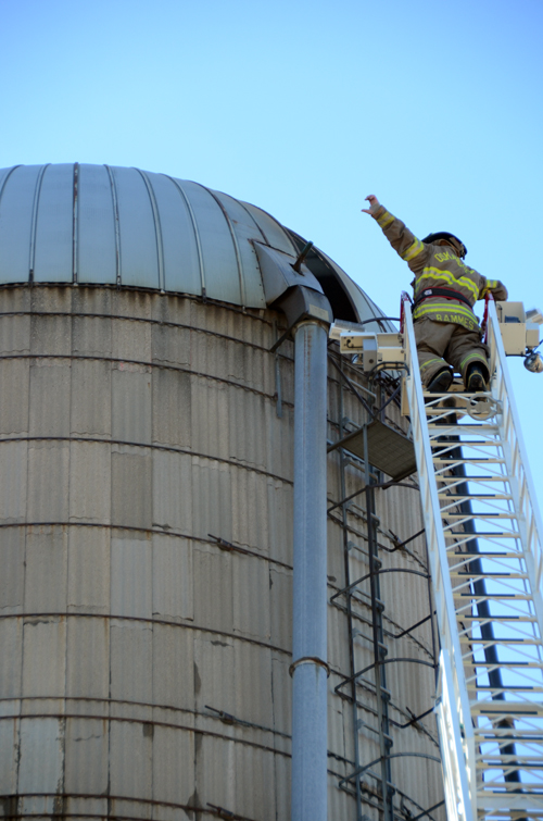 Oskaloosa firefighter Jared Bammes made one last run up the ladder to check the interior of a silo after the application of water and foam appeared to be successful at snuffing out a fire. Bammes brought the ladder truck at the request of District 11 in order to reach the top of the silo.