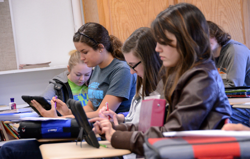 In today's classroom students are likely to be concentrating on one item—the iPad. This digital device contains their lesson plan, the textbook, a library, and tells them how many times they have been tardy this year. These history students from right to left are Brylee Coleman, Maclaine McKnight, Carly Tillery, and Sierra Vessar.