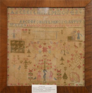 This cross-stitch piece of work is the oldest item in the museum. It dates back to 1841, which makes it older than the state of Kansas. It was made by Mariah Robinson and was donated by the Caroline Bickley Estate.