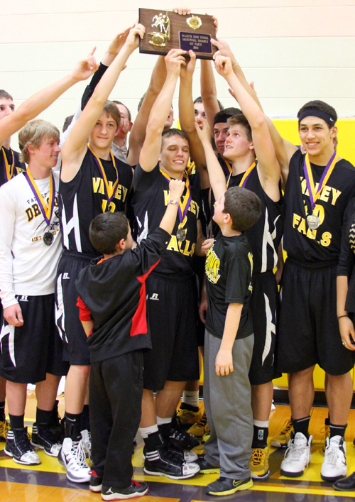 A jubilant Dragon team hoists the McLouth Invitational Tournament trophy after defeating the host team, 84-77, in what was a hard-fought contest.