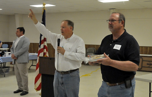 Ron Ellis, center, secretary of the Jefferson County Republican Central Committee, handles bids from the floor on a pie as Oskaloosa's Dave Taylor of Colonial Acres Guesthouse & Floral, right, assists him while Travis Oliver, chairman of the central committee, looks on.